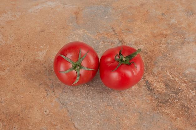 Due pomodori freschi isolati sulla tavola di marmo.