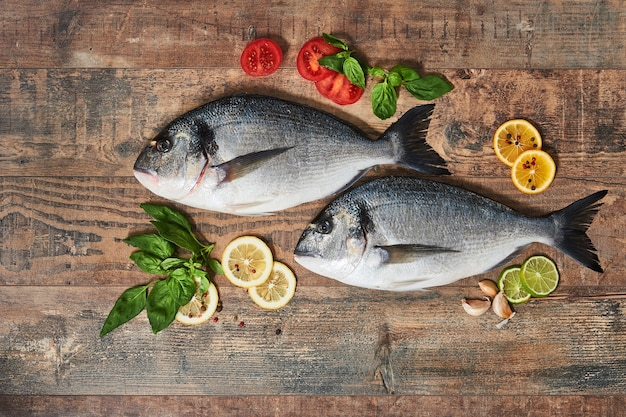 Two fresh uncooked dorado with lemons, herbs, tomatoes and spices on wooden table. top view