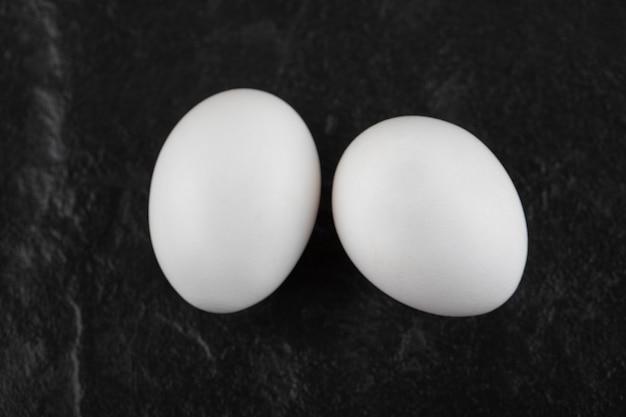 Два свежих белых куриных яйца на черном столе.