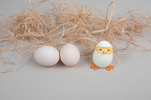 Due uova di gallina bianche fresche con pollo giocattolo e fieno.