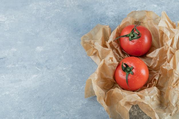 羊皮紙に2つの新鮮な丸ごとトマト。