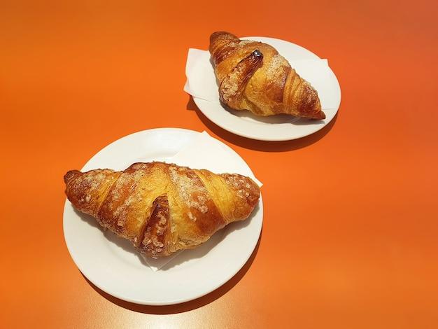 Два свежеиспеченных круассана лежат на белых блюдцах на апельсиновом столе.