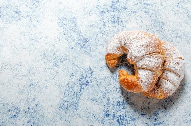 Two freshly baked croissants with icing sugar on a blue background with texture