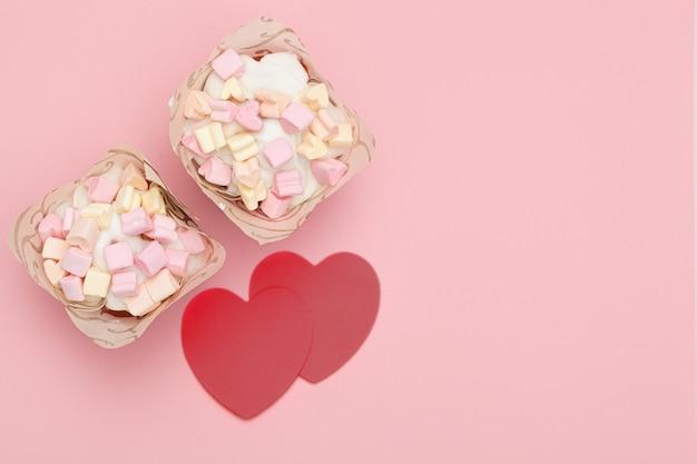甘いアイシングとハート型のマシュマロで覆われた焼きたてのカップケーキ2つと、ピンクの背景に赤いハート2つ。テキストの場所。バレンタイン・デー