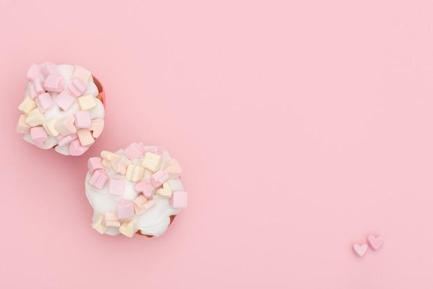ピンクの背景に甘いアイシングとハート型のマシュマロで覆われた2つの焼きたてのカップケーキ。テキストの場所。バレンタイン・デー