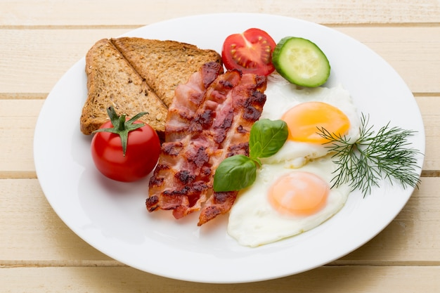 Two fried eggs and bacon for healthy breakfast . selective focus Premium Photo