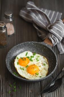 어두운 나무 바탕에 작은 냄비에 두 개의 튀긴 된 계란.
