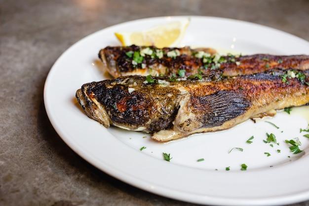 레몬 근접 촬영으로 하얀 접시에 두 개의 튀긴 바다 고비 물고기