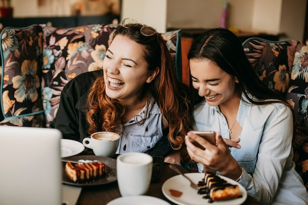 Two friend having fun laughing while sitting in a cafe .
