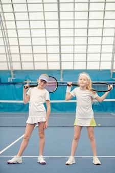 カメラの前のスタジアムのテニスフィールドに立って、プレーの準備ができて肩にラケットを持っている白いスポーツウェアの2人のフレンドリーな女の子