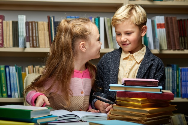 Two friendly school kids discussing a book while reading in library, education concept. child brain, knowledge