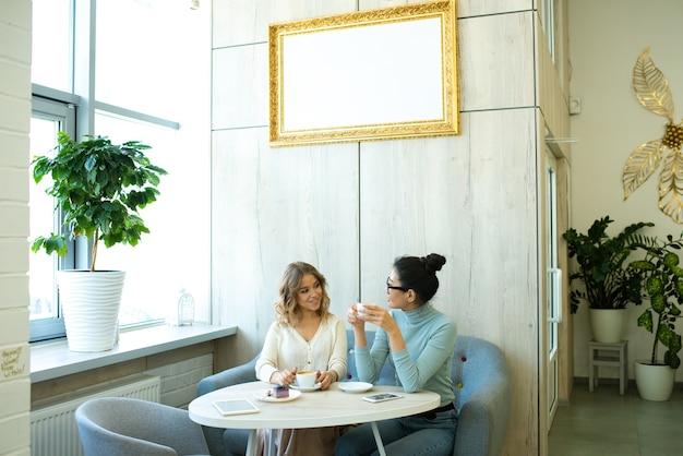 カフェのテーブルのそばの柔らかく快適なソファに座って、コーヒーを飲み、相互作用するカジュアルウェアの2人のフレンドリーな若い女性