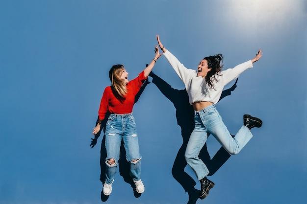 青い壁の前で楽しくジャンプするジーンズの金髪とブルネットの2人の友人