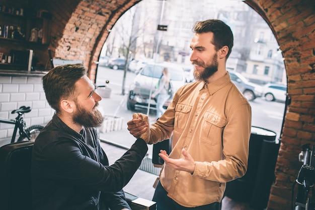 Двое друзей в парикмахерской. они пожимают друг другу руки. ребята улыбаются друг другу.