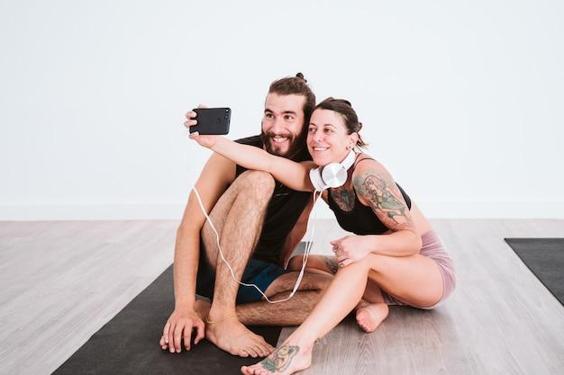 ジムで2人の友人が携帯電話とヘッドセットでselfieを取り、楽しんでいます。スポーツとテクノロジーのコンセプト