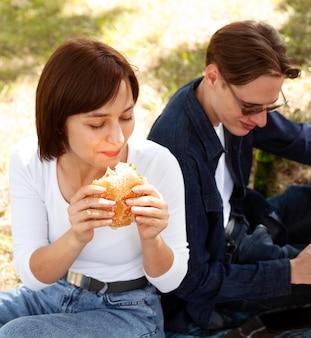 Двое друзей в парке едят гамбургер