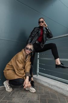 거리에서 포즈를 취하는 가죽 트위스트와 청바지를 입은 세련된 옷을 입은 아름다운 젊은 여성 두 명