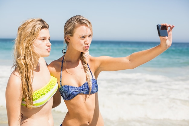 Two friends in bikini taking a selfie