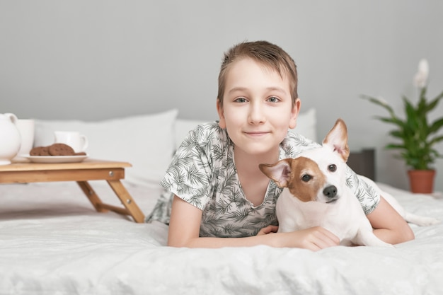 Two friends boy and dog lying together on bed. boy on bed with dog jack russell terrier. friendship concept.