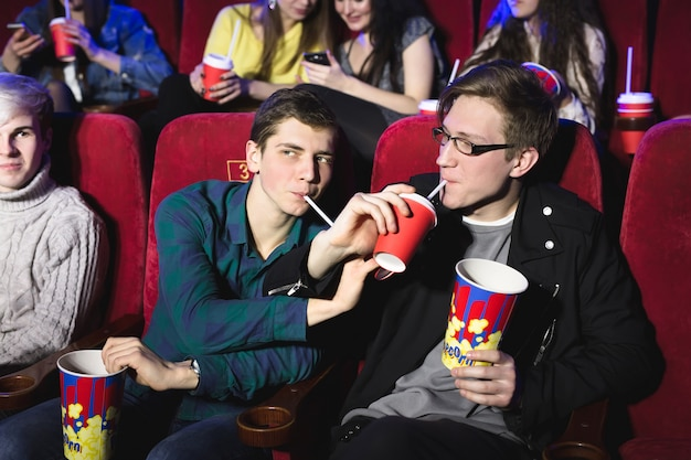 Two friends, brothers drink through a tube in the cinema.