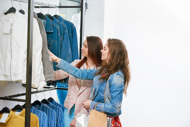 Two friends buying clothes in the shop.