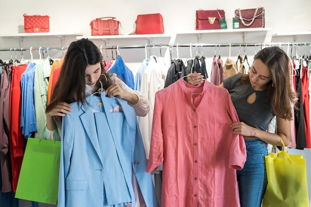 의류 부티크에서 새 옷을 선택하는 두 친구. 구매 및 판매