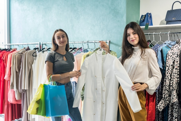 Two friends choosing a new cloth in a clothing boutique. buy and sale