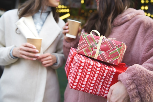 Two friends on christmas market carrying christmas presents