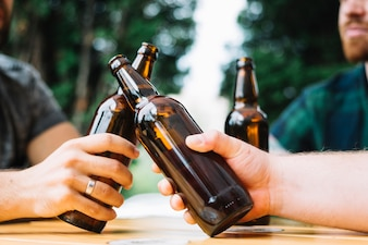 Two friends clinking the bottles of beer over the table