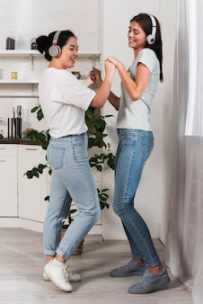 Two friends dancing at home with music on headphones