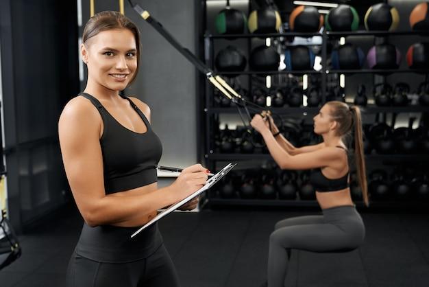 Trx 시스템으로 운동 운동을하는 두 친구