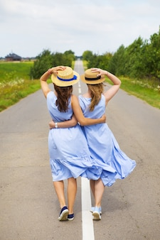 Two friends in dresses and hats stand in an embrace on the asphalt road