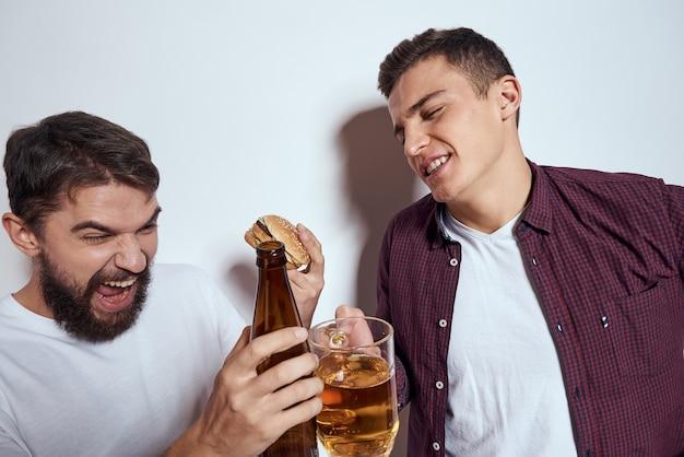 Двое друзей пьют пиво, отдых, развлечения, алкоголь, дружба, образ жизни, светлый фон. фото высокого качества