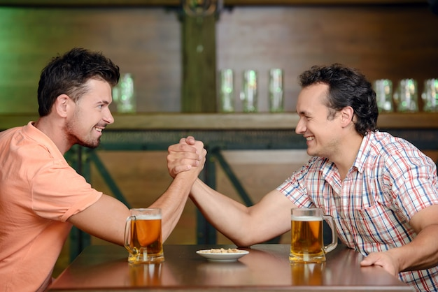 Two friends drinking beer and having fun at the pub.