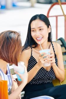 屋外でカクテルを飲む2人の友人