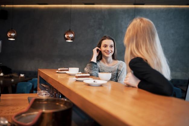 Два друга наслаждаются кофе вместе в кафе, когда они сидят за столом в чате