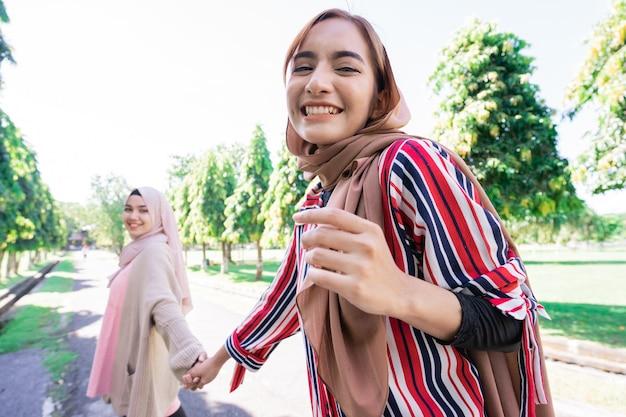 夏の太陽を楽しみ、公園を歩いて手をつないでいる2人の友人