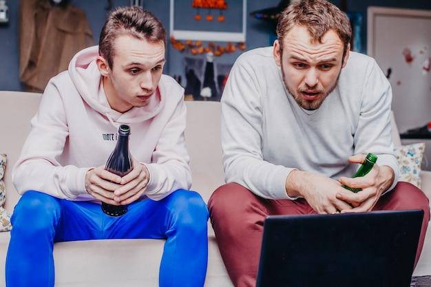 Двое друзей фанатов с пивом смотрят футбол