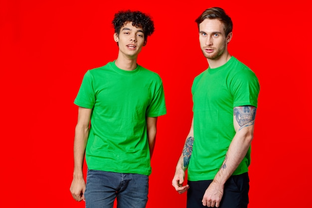 Two friends in green tshirts communication red background studio