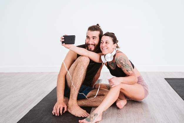 Two friends at the gym taking a selfie with mobile phone and headset and having fun. sport and technology concept