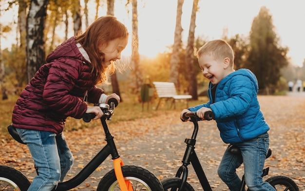 자전거를 타고 공원에서 저녁 산책을하는 두 친구가 아무것도 신경 쓰지 않고 즐겁게 놀고 있습니다.