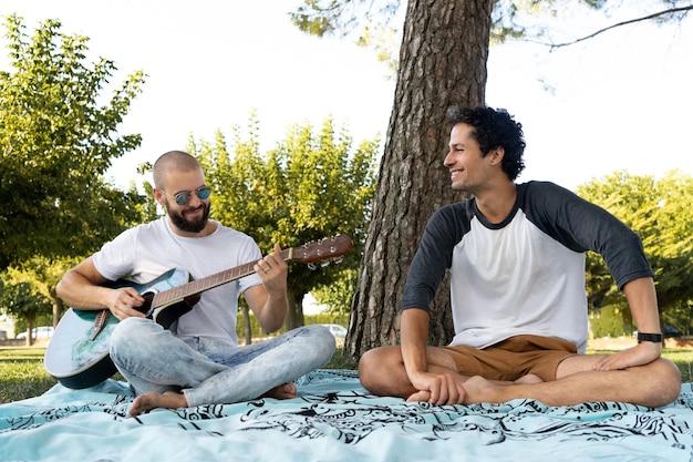 Два друга веселятся и играют на гитаре в парке