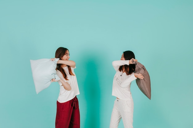 Two friends having pillow battle