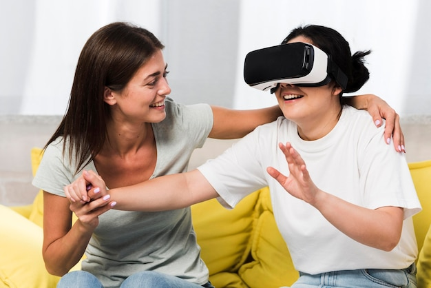 Two friends at home using virtual reality headset