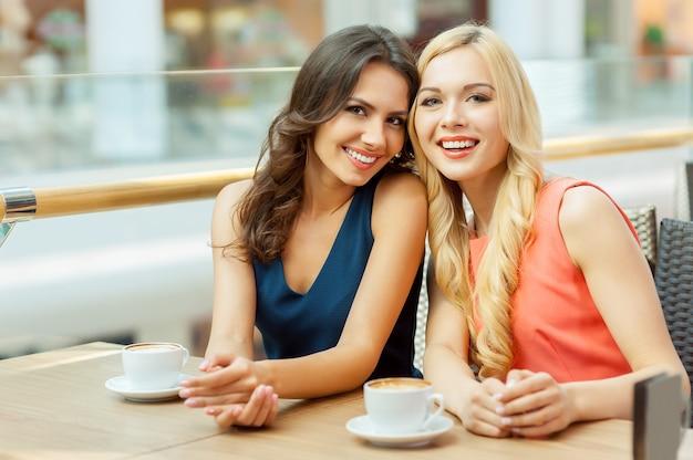 Двое друзей в кафе. две молодые подруги сидят в кафе и смотрят в камеру