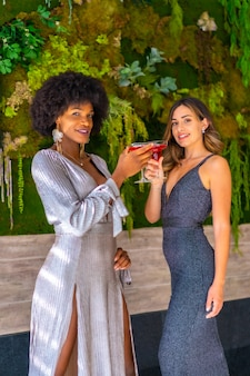 Двое друзей в праздничных платьях пьют коктейль на вечеринке в отеле, образ жизни. гламурный образ жизни, эксклюзивная вечеринка
