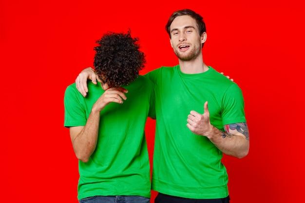 緑のtシャツを着た2人の友達が楽しい抱擁