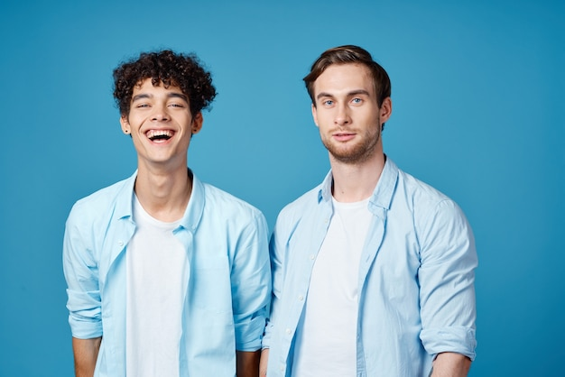Два друга в одинаковых рубашках и футболке, жестикулирующие руками на синем фоне