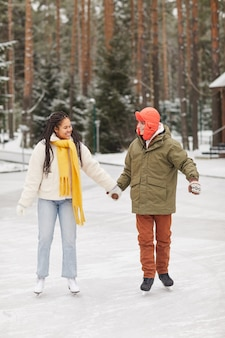 屋外スケートリンクで一緒にスケートを学ぶ暖かい服を着た2人の友人