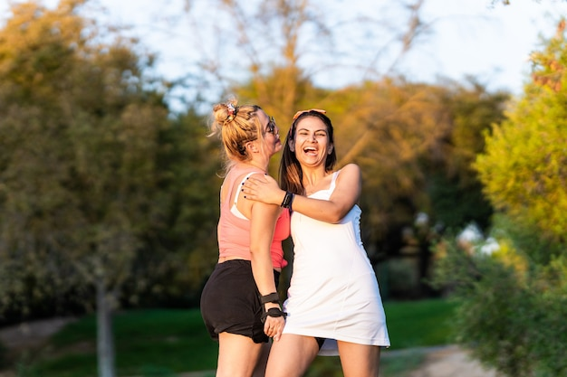 Два друга смеются, стоя в парке